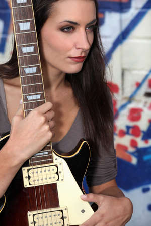 young woman holding a guitar photo