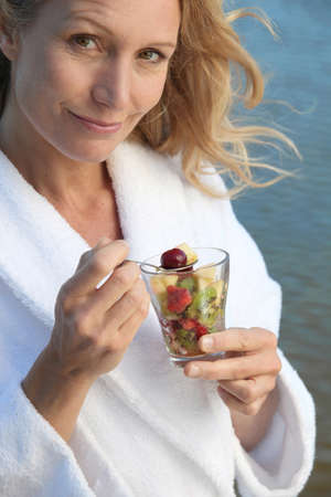fruity salad: Woman eating a glass of fruit salad