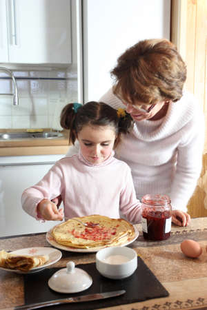 Woman and child making pancakes photo