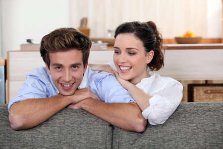 Young couple leaning on the back of their sofa photo
