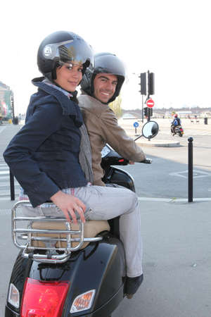 crash helmet: a couple riding a scooter Stock Photo