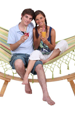 Young couple sitting in a hammock with drinks photo