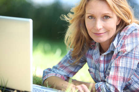 35 39 years: Woman using laptop computer in the park Stock Photo