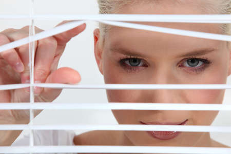 discreet: a blonde woman looks through blinds Stock Photo