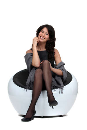 miniskirt: Elegant woman sitting in white chair Stock Photo