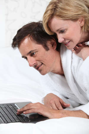 45 55 years: Couple on laptop in dressing gown. Stock Photo