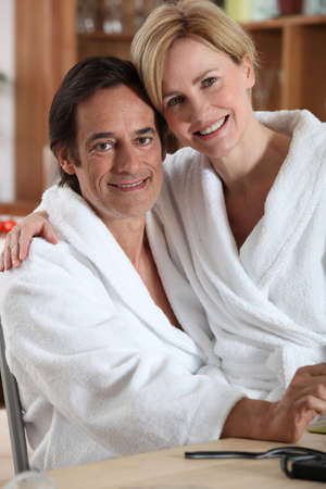 toweling: Woman in a bathrobe, sitting on her partner