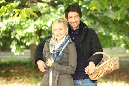 young couple behind trees in autumn, man holding a wickerwork basket photo