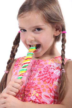 sucking lollipop: little girl with plaits sucking lollipop Stock Photo