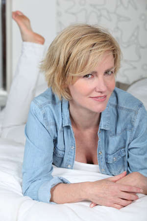 mistress: Dressed woman lying on a made bed Stock Photo