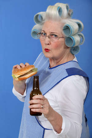 funny picture of grandma with hair curlers relishing cheeseburger with beer Stock Photo