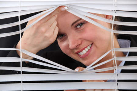 Happy woman peering through blinds photo