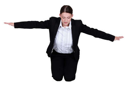 Kneeling businesswoman with arms stretched photo