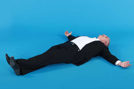 hands behind head: mature man in suit lying on his back with arms wide apart against blue background