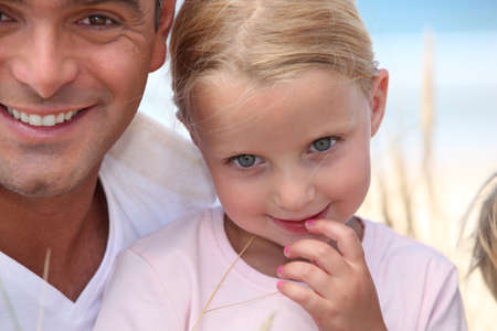 beautiful blonde girl with green eyes: A father and his daughter at the beach. Stock Photo
