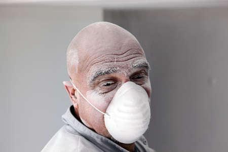 smoothen: Bald plasterer covered in dust