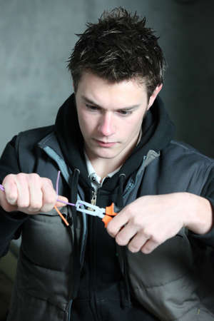 young electrician using pliers photo