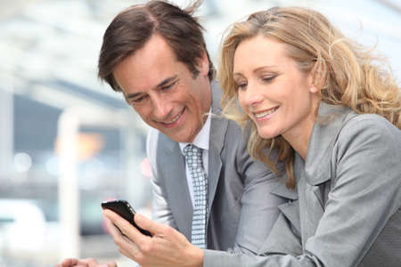 businessman and woman with phone photo