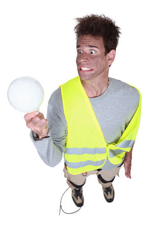 Funny electrician holding replacement bulb photo