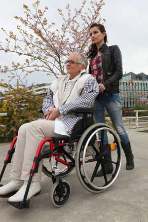 man pushing: Young woman pushing an elderly lady in a wheelchair