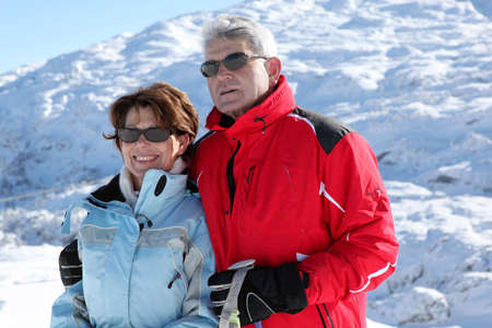 50 to 55 years old: Older ski couple on a mountain