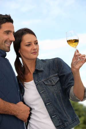 Couple tasting wine in field photo
