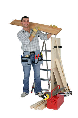 A handyman carrying a wooden plank Stock Photo - 11830500