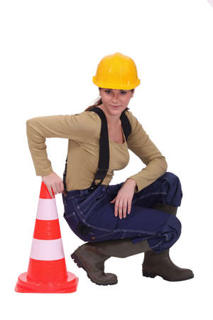 Tradeswoman kneeling next to a pylon photo