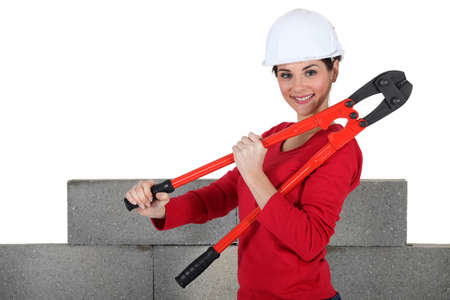 erecting: female builder holding bolt cutters