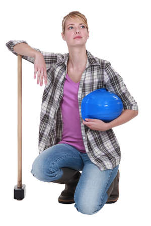 workwoman: A kneeling tradeswoman holding her head up high