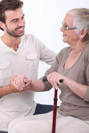 personas ayudando: Hombre joven ayudando a la mujer mayor