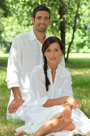look pleased: man and woman sitting in the forest