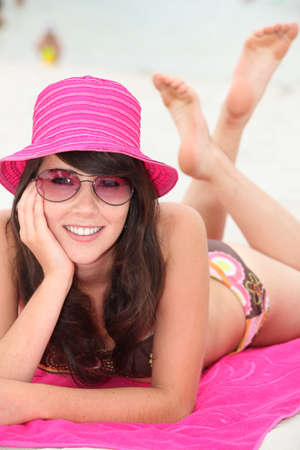 Young woman lying on the beach in  bikini and a bright pink hat photo