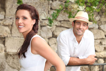 Couple standing by a stone wall photo