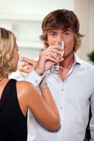 Young couple drinking champagne with their arms entwined photo