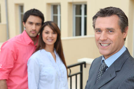 Estate agent with young couple photo