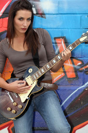 likeness: Female guitarist stood by painted wall Stock Photo