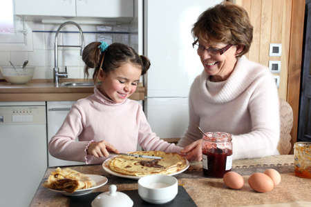 granddaughter: Young girl preparing crepes with her grandmother Stock Photo