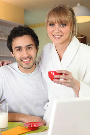 Couple having breakfast in front of their laptop photo