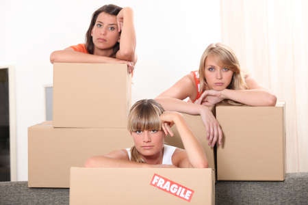slumped: Three woman leaning on brown cardboard boxes Stock Photo