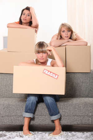 stood up: Three housemates with boxes Stock Photo