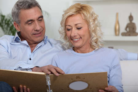 Middle-aged couple looking through photo-album photo