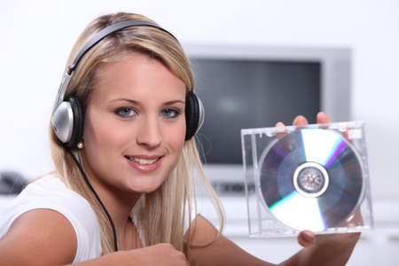 a blonde woman listening music and showing a cd photo