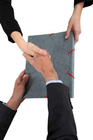 la union hace la fuerza: Dos hombres de negocios d�ndose la mano sobre el documento