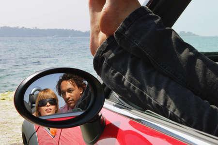 top down car: Couple sat in car at the beach