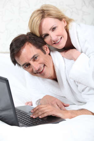 Happy couple on laptop in dressing gown. photo