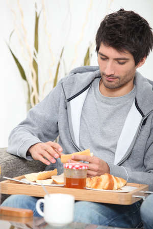 eating breakfast: portrait of a young man at breakfast