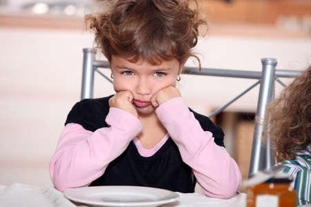 sulk: Sulky girl sitting at the breakfast table