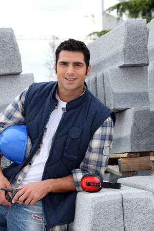 ear checked: Construction worker stood holding hard hat