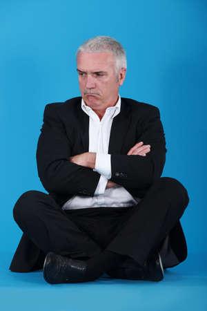 sulk: Grumpy man sitting on the floor